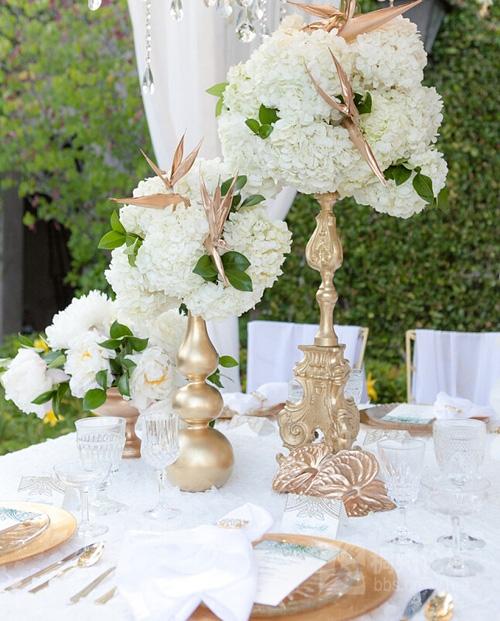 餐桌布置为了打造花园感,搭建了一个棚子,用白色的帷幔四周围绕,在顶端挂满了花材。华丽的欧式水晶吊灯穿梭期间,清新脱俗的绿白点缀上柔情热烈的阳光色,让整个婚礼简洁优雅且浓情漫漫。